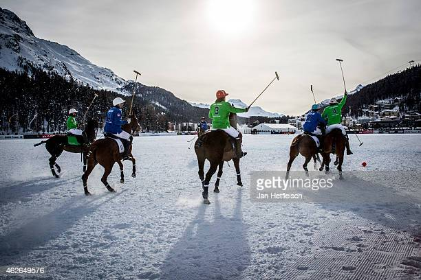 Members of the 'Trois Pommes' team battle for the ball with team 'BMW' during the Snow Polo World Cup 2015 on January 31 2015 in St Moritz Switzerland