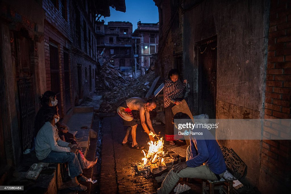 Members of the Tsayana family warm themselves next to a fire outside their damaged home house on May 3, 2015 in Bhaktapur, Nepal. A major 7.8 earthquake hit Kathmandu mid-day on Saturday, and was followed by multiple aftershocks that triggered avalanches on Mt. Everest that buried mountain climbers in their base camps. Many houses, buildings and temples in the capital were destroyed during the earthquake, leaving over 6000 dead and many more trapped under the debris as emergency rescue workers attempt to clear debris and find survivors. Regular aftershocks have hampered recovery missions as locals, officials and aid workers attempt to recover bodies from the rubble.