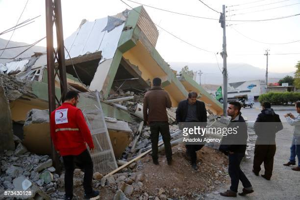 Members of the Turkish Red Crescent who reached the region as a first response observe a collapsed building in Derbendihan district of Sulaymaniyah...