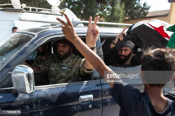 Members of the Turkishbacked Free Syrian Army a militant group active in parts of northwest Syria patrol the Turkish side of the border between...