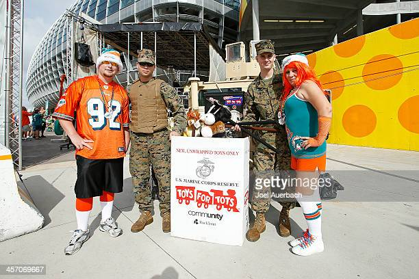 Members of the U S Marine Corps Reserve collect toys from Miami Dolphins for their Toys for Tots program prior to the game against the New England...