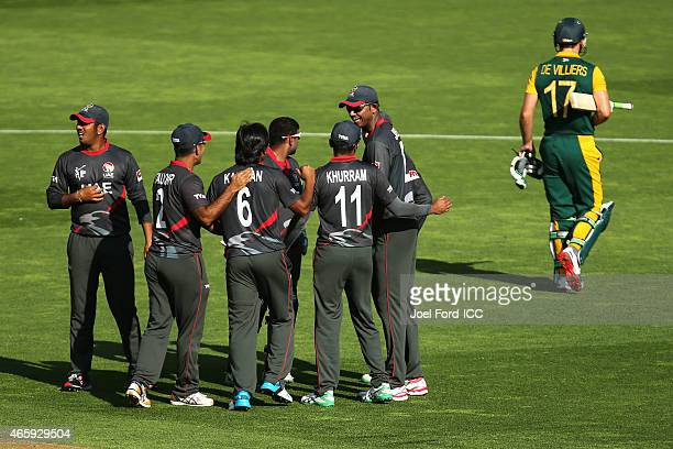 Members of the UAE cricket team celebrate taking the wicket of AB de Villiers of South Africa during the 2015 ICC Cricket World Cup match between...