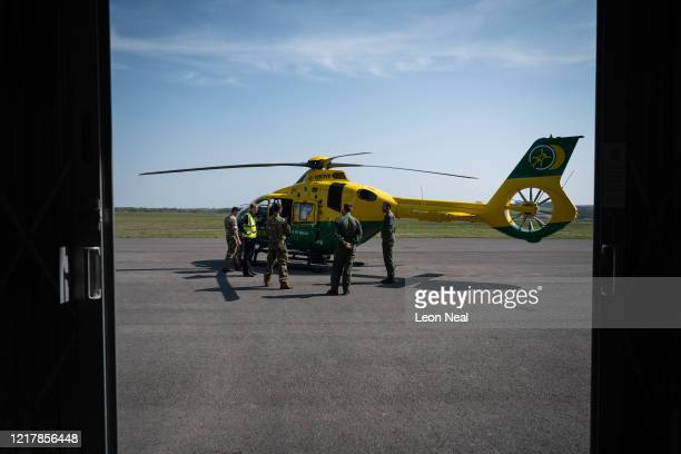 Members of the UK Armed Forces talk with NHS medical staff and Air Ambulance Service crews next to the Hampshire and Isle of Wight air ambulance...