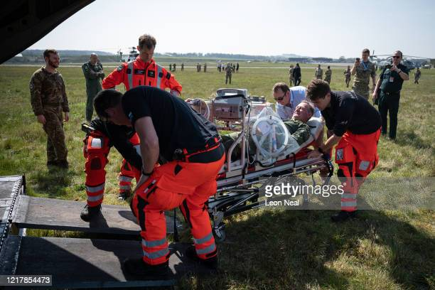 Members of the UK Armed Forces work with NHS medical staff and Air Ambulance Service crews as they load a stretcher onto a Boeing CH47 Chinook...