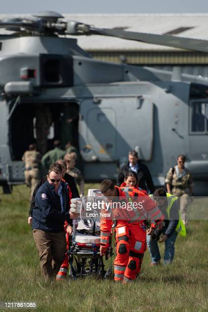 Members of the UK Armed Forces work with NHS medical staff and Air Ambulance Service crews as they push a stretcher after testing the loading of an...