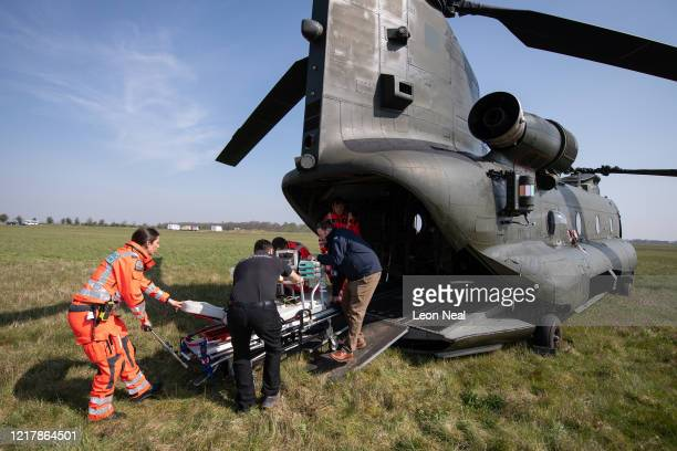 Members of the UK Armed Forces work with NHS medical staff and Air Ambulance Service crews as they remove a stretcher from a Boeing CH47 Chinook...