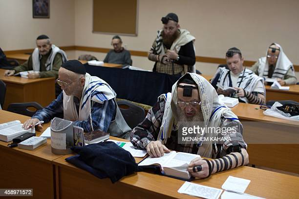 Members of the Ukrainian Jewish community wearing prayer shawls and phylacteries pray in the only synagogue in the eastern Ukrainian city of Donetsk...
