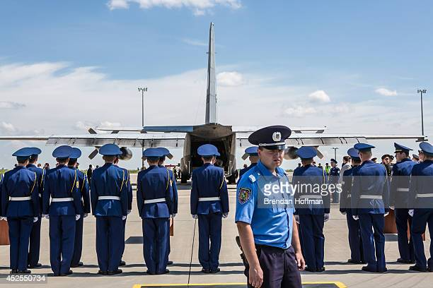 Members of the Ukrainian military stand to attention after coffins containing the bodies of victims of the crash of Malaysia Airlines flight MH17...