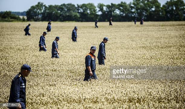 Members of the Ukrainian State Emergency Service search for bodies in a field near the crash site of the Malaysia Airlines Flight MH17 near the...