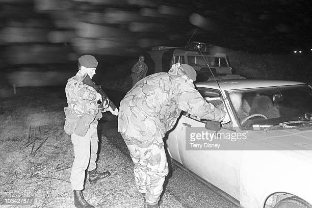 Members of the Ulster Defence Regiment search a car at a checkpoint while on patrol in County Down Northern Ireland on February 05 1984