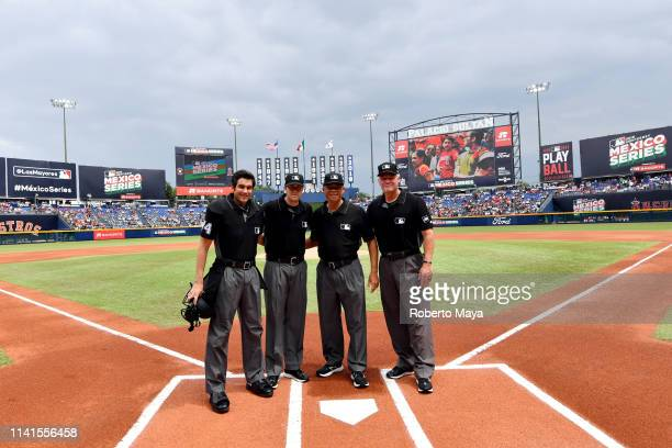 Members of the umpiring crew pose for a photo at home plate prior to the game between the Houston Astros and the Los Angeles Angels at Estadio de...