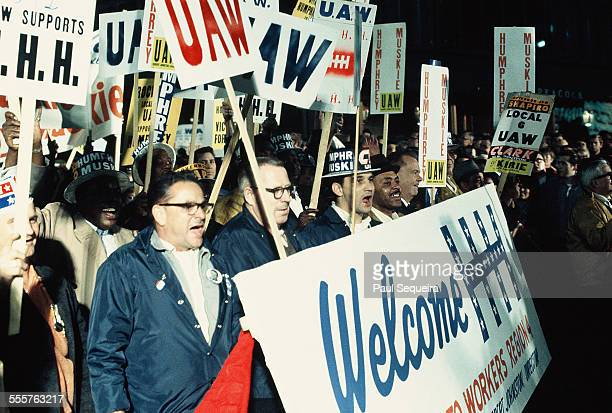 Members of the United Auto Workers union march along a city street carrying signs of support for Presidential candidate Hubert Humphrey Chicago...