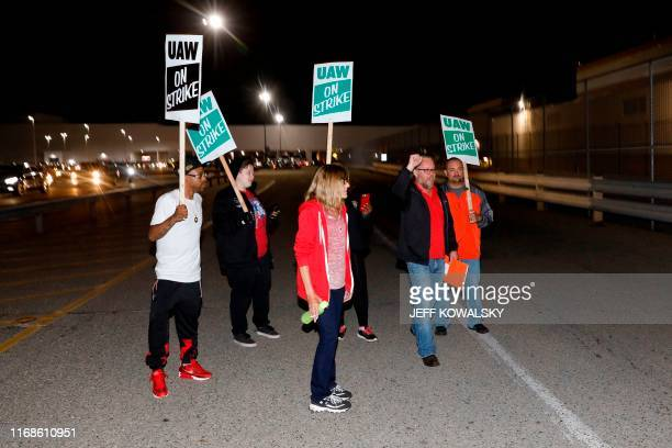 Members of the United Auto Workers who are employed at the General Motors Co Flint Assembly plant in Flint Michigan walk out of the plant holding...