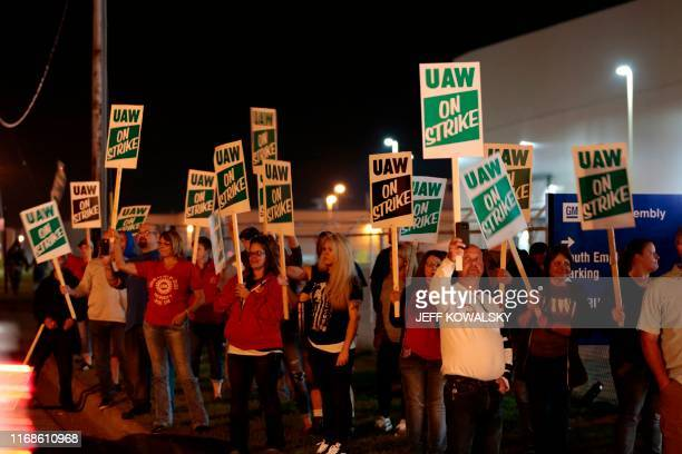 Members of the United Auto Workers who are employed at the General Motors Co Flint Assembly plant in Flint Michigan hold signs and react as workers...