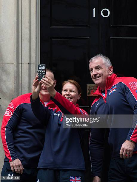 Members of the United Kingdom team attending the Invictus Games take selfies at 10 Downing Street before meeting British Prime Minister David Cameron...