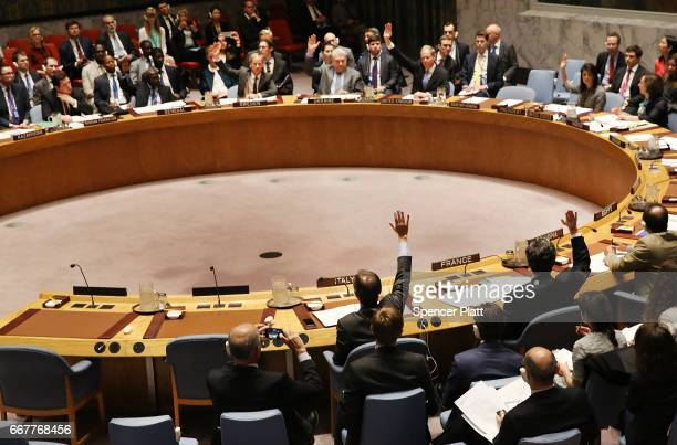 Members of the United Nations Security Council hold a vote on a draft resolution demanding that the Syrian government cooperate with an investigation...