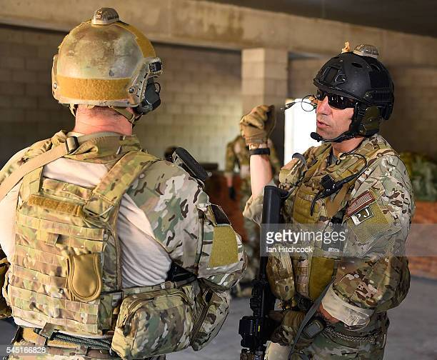 Members of the United States Air Force 129th Pararescue Squadron discuss tactics as other members treat simulated wounded soldiers following a...