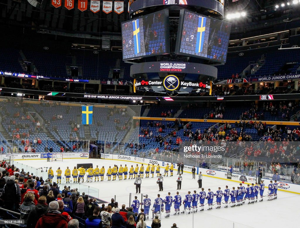 Members of the United States and Sweden watch as the Swedish Flag is raised in celebration of Sweden's 4-2 win in the IIHF World Junior Championships Semifinal game at KeyBank Center on January 4, 2018 in Buffalo, New York.