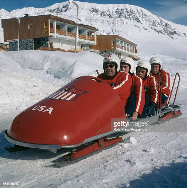 Members of the United States bobsled team posed in their bobsled beside the course of the bobsleigh competition at the 1968 Winter Olympics in...