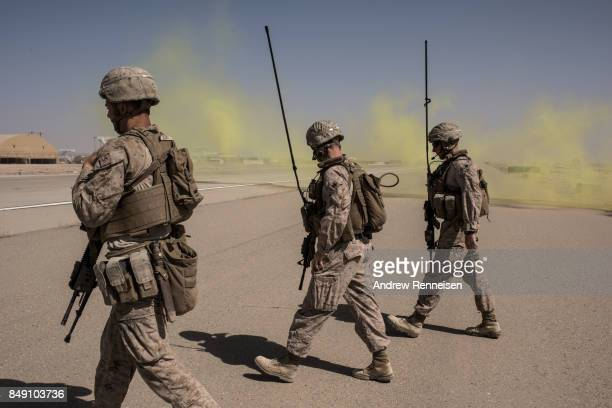 Members of the United States Marine Corp Task Force South West walk across a runway after marking a location for an airdrop of cargo on September 10...