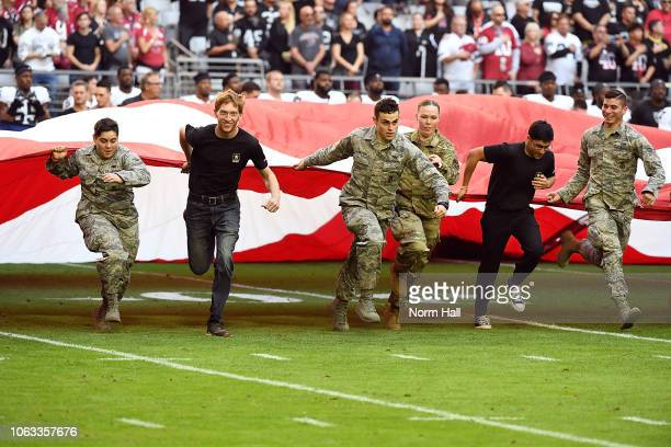 Members of the United States Military run onto the field while holding a giant US flag during the singing of the national anthem prior to the start...