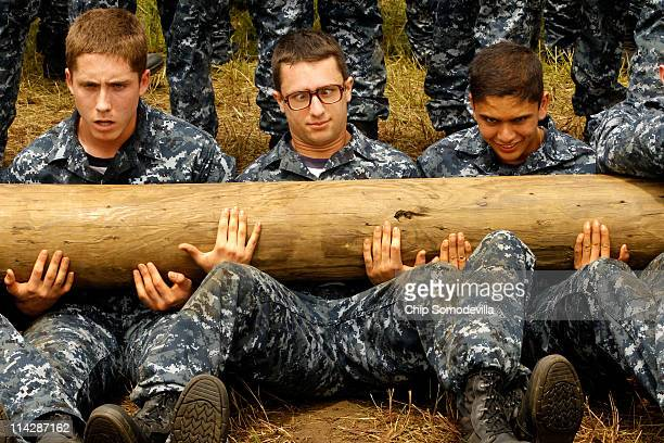 Members of the United States Naval Academy freshman class do situps as a team with heavy logs during the rigorous Sea Trials May 17 2011 in Annapolis...