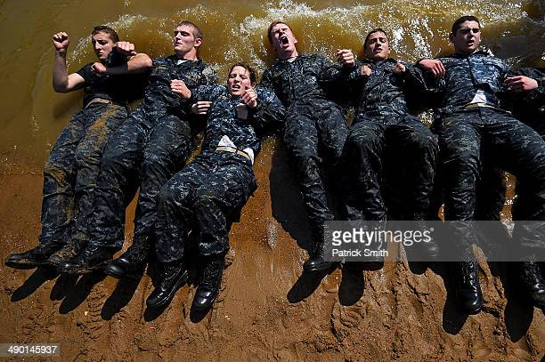 Members of the United States Naval Academy freshman class do situps at the wet and sandy station during the annual Sea Trials training exercise at...