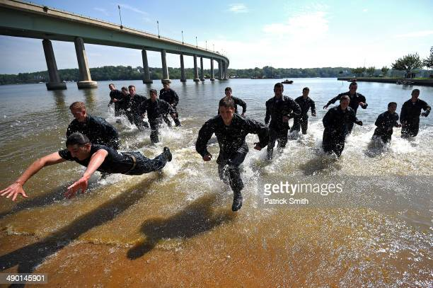 Members of the United States Naval Academy freshman class race to the sand at the wet and sandy station during the annual Sea Trials training...