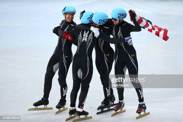 Members of the United States short track team celebrate winning the bronze medal in the Short Track Men's 5000m Relay on day fourteen of the 2014...