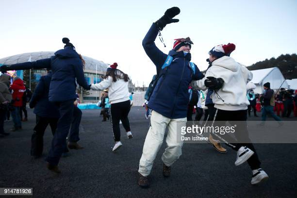 Members of the United States team dance with performers after the team's flag raising ceremony during previews ahead of the PyeongChang 2018 Winter...