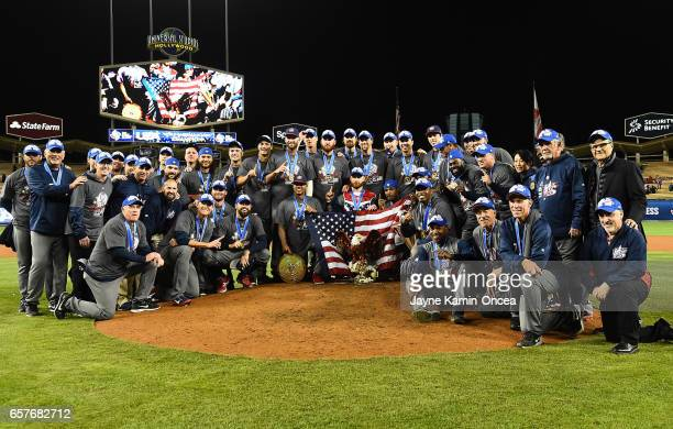 Members of the United States team pose for a photo on the pitcher's mound after defeating Puerto Rico in the 2017 World Baseball Classic at Dodger...