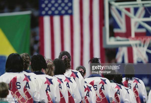Members of the United States Women's basketball team look toward the Stars and Stripes flag at the playing of the national anthem following their the...