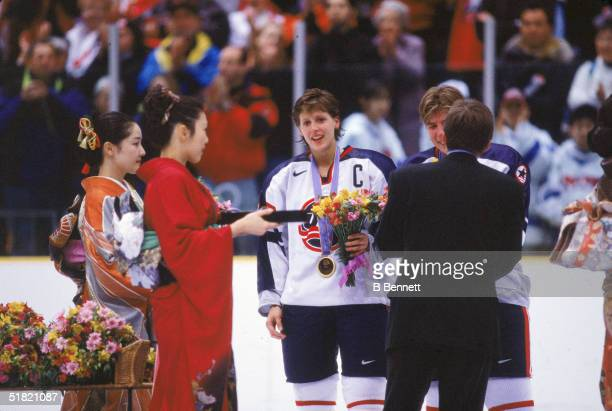 Members of the United States women's hockey team stand as an unidentified man in a suit and two women in kimonos award them medals and flowers after...
