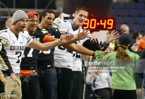 Members of the University of Colorado football team congratulate finishers of the 5K race inside the 1stBank Center in Broomfield Jordan Gehrke...