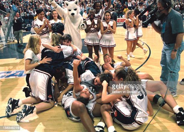 Members of the University of Connecticut women's basketball team celebrate after their victory in the regional final during a game against Virginia...