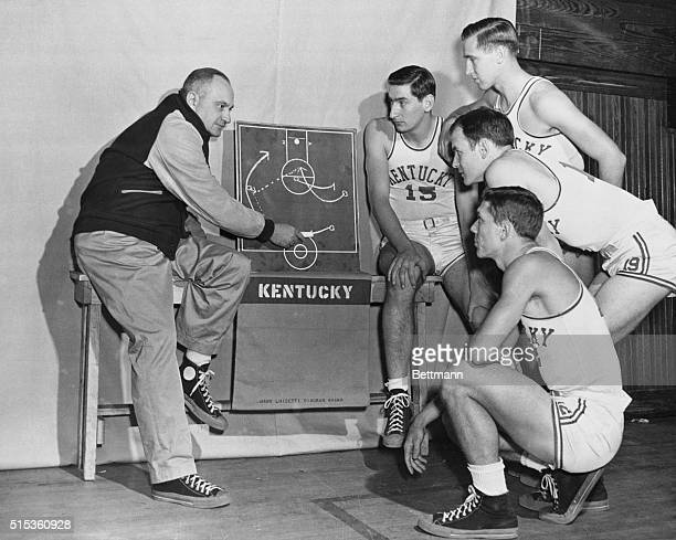 Members of the University of Kentucky basketball team left to right Alex Groza Jim Jordan Jack Parkinson and Ralph Beard listen to coach Adolph Rupp...