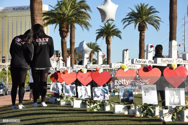 Members of the University of Las Vegas pom squad visit 58 white crosses for the victims of Sunday night's mass shooting on the Las Vegas Strip just...