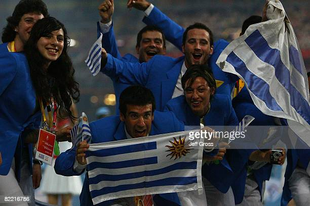 Members of the Uruguay delegation wave their flags as they enter during the Opening Ceremony for the 2008 Beijing Summer Olympics at the National...