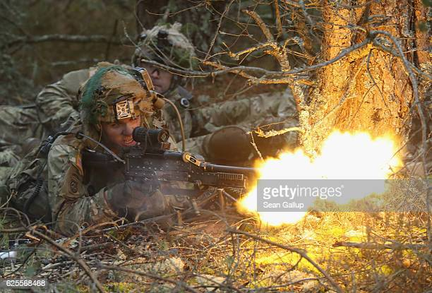 Members of the US 173rd Airborne Brigade fire blanks from a machine gun during a simulated attack during the Iron Sword multinational military...