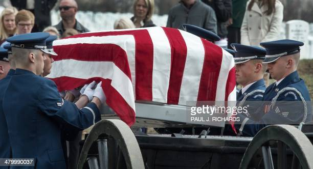 Members of the US Air Force Honor Guard reach out and adjust the US flag before off loading the casket from the caisson bearing the remains of seven...