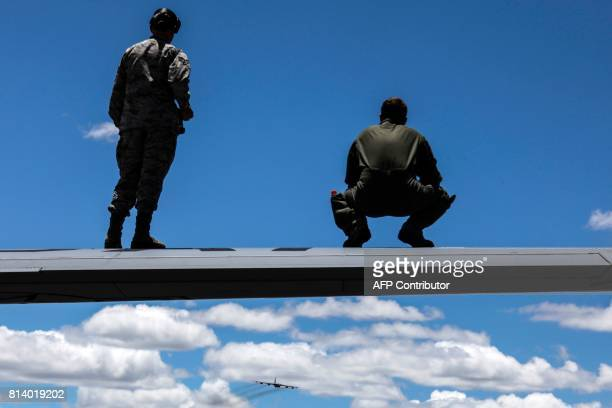 Members of the US Air Force look at a B52 airplane as it performs during the FAir Colombia 2017 air festival at the Jose Maria Cordova airport in...
