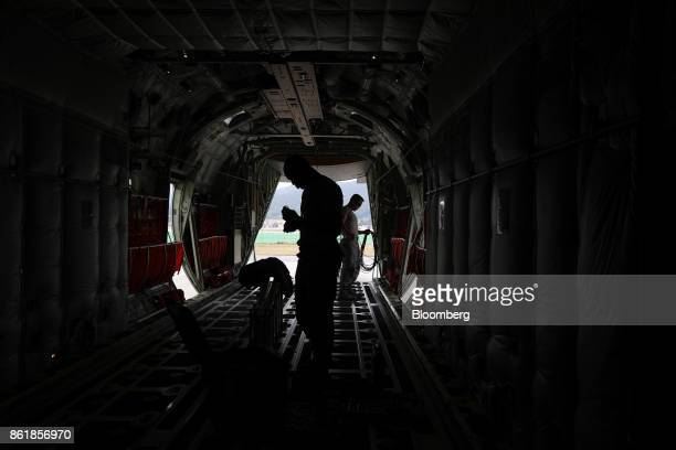 Members of the US Air Force stand inside the C130J Super Hercules turboprop military transport aircraft manufactured by Lockheed Martin Corp during a...
