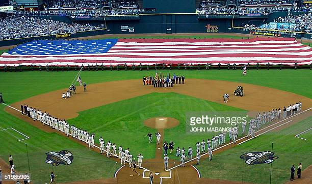 Members of the US armed forces display a giant American Flag during ceremonies before game one of the 2001 World Series between the New York Yankees...