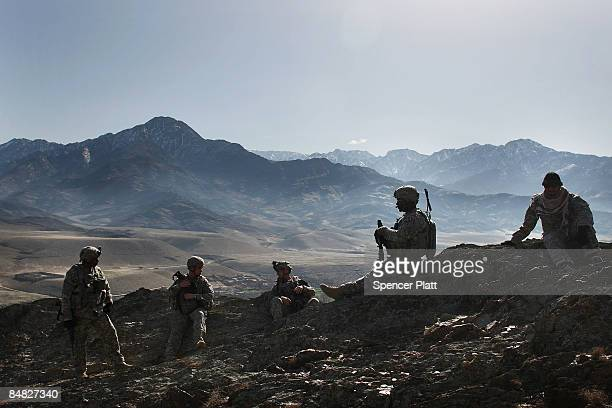 Members of the US Army 16 Field Artillary Unit and the 2nd Squad 1st Platoon 527 MP Company rest while searching for caves where insurgents are...