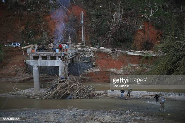 Members of the US Army 1st Special Forces Command deliver boxes of MRE's and water up a makeshift ladder to people that were cut off after the bridge...