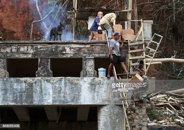 Members of the US Army 1st Special Forces Command deliver boxes of MRE's and water to people that were cut off after the bridge collapsed when...