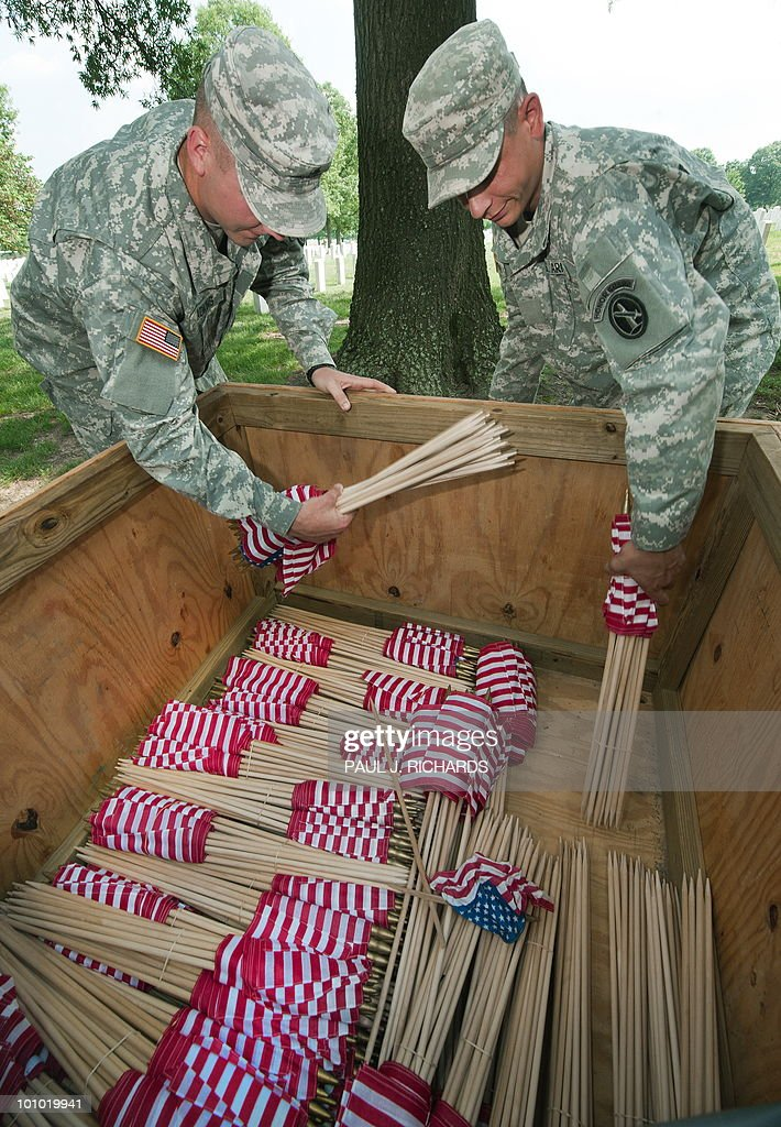 Members of the US Army 3rd US Infantrly Regiment, 'The Old Guard,' grab the last of thousands of flags to be placed at US military member's gravestone in Arlington National Cemetery's Section 60, where many of the US Iraq and Afghanistan casualities are burried, May 27, 2010, in advance of this year's Memorial Day national holiday. AFP Photo/Paul J. Richards