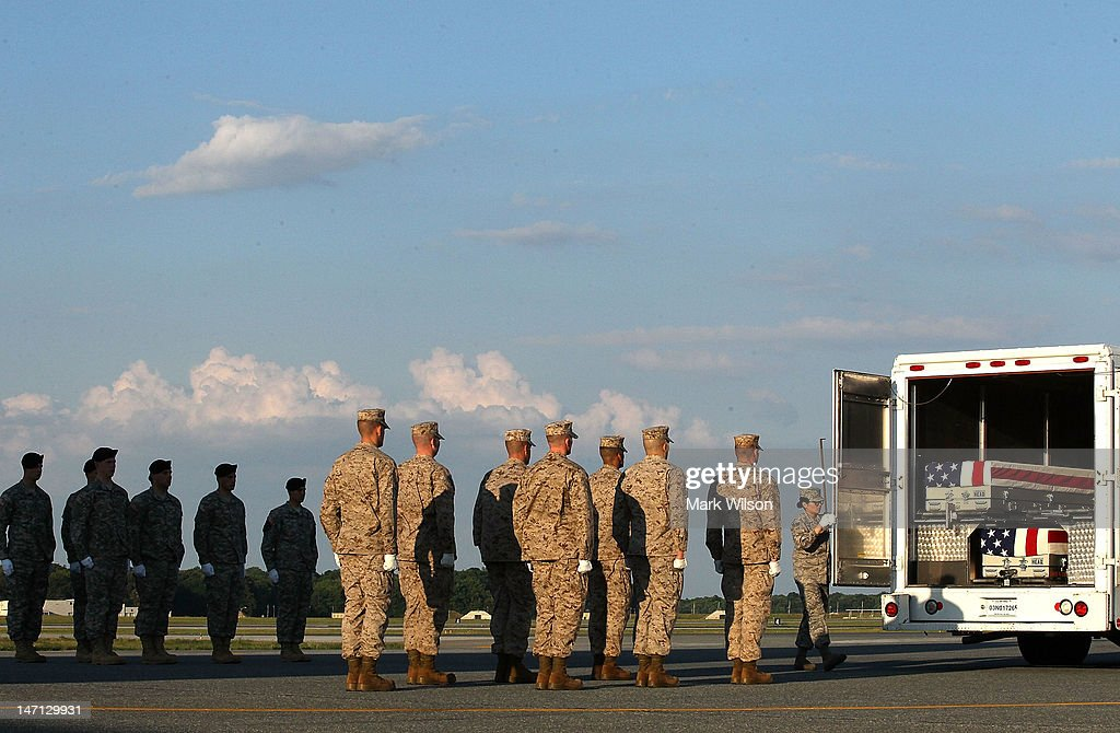 Members of the U.S. Army and U.S. Marines watch as the door closes on three fallen soldiers during a dignified transfer at Dover Air Force Base, on June 25, 2012 in Dover, Delaware. U.S. Army Major Paul Voelke, U.S. Marine Eugene C. Mills III, and U.S. Marine Steven P. Stevens II, were killed while conducting combat operations in Afghanistan.
