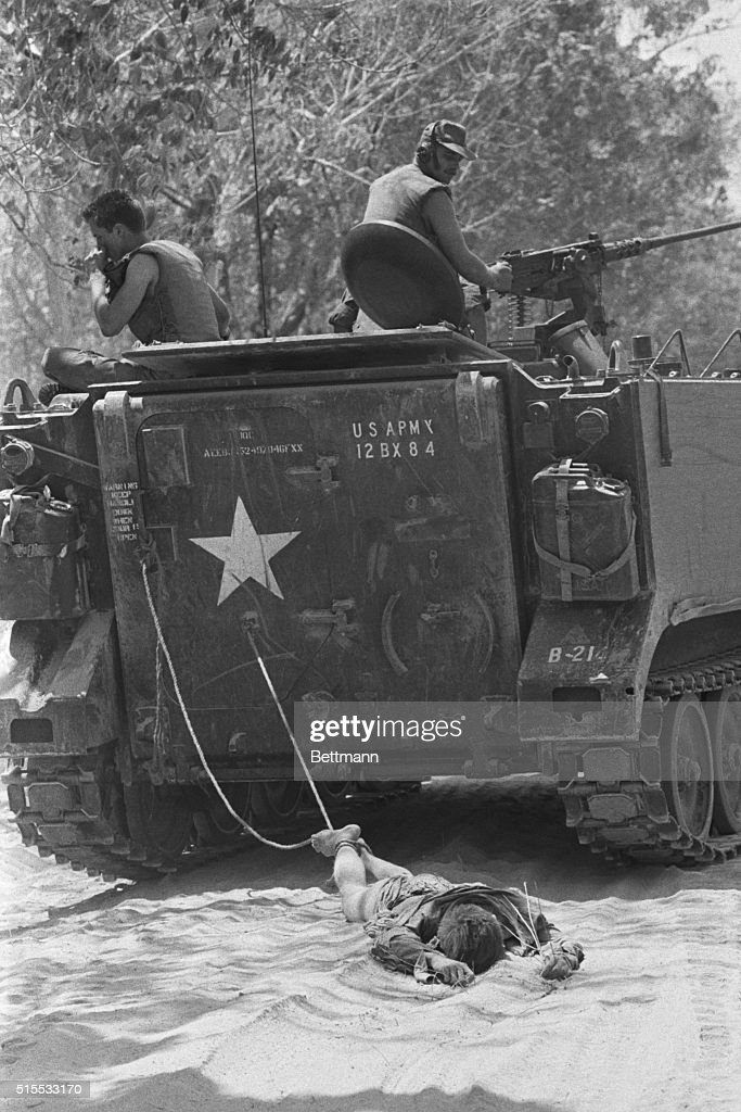 American Soldiers Dragging Body of Vietcong Soldier : News Photo