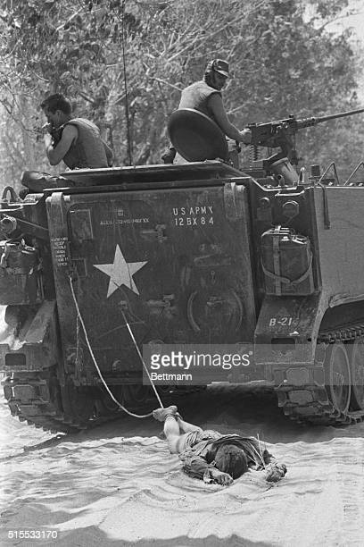 Members of the US Army drag the body of a dead Vietcong soldier from their armored vehicle following a Vietcong night attack against the defensive...